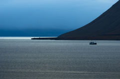 Isfjorden. A fishing boat is returning home from Barents Sea in the morning light Stock Image