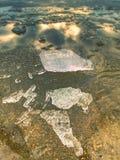 Isfragment på den tomma sandiga kusten fryst sand på floden seglar utmed kusten Arkivbild