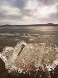Isfragment på den tomma sandiga kusten fryst sand på floden seglar utmed kusten Royaltyfria Foton