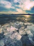 Isfragment på den tomma sandiga kusten fryst sand på floden seglar utmed kusten Royaltyfri Bild