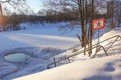 Ishålet i sjön i vinter utrustas med en stege för lansering förbudtecken med inskriften: gå inte på royaltyfria bilder