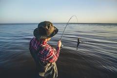 Isherman с рыболовной удочкой в его руке и уловленной рыбе стоит в воде стоковое фото