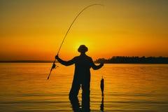 Isherman с рыболовной удочкой в его руке и уловленной рыбе стоит в воде стоковое изображение