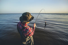 Isherman with a fishing rod in his hand and a fish caught stands in the water Stock Photo