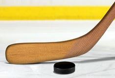 Ishockeypinne och puck på isbana Arkivfoton