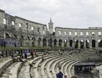 Iside of Amphitheater 1st century AD in Pula. People on the step. S and tower. Cloudy day in the summer stock photography