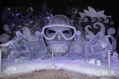 Isinstallation Undervattens- fantasi av djupfryst is i form av en dykare i en maskering arkivfoto