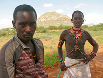 ISIOLO, KENYA - NOVEMBER 28, 2008: Two unknown men from the trib. E Tsonga in national dress closeup in Isiolo, Kenya - November 28, 2008. Mountains in the Stock Photography