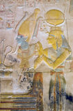 Isis and Osiris carving. Ancient Egyptian painted and carved image of the gods Osiris seated with Isis behind him. Isis is wearing the horned crown of Hathor royalty free stock image