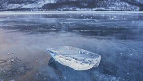 Isisflaket roterar på isen mot bakgrunden av det fantastiska berglandskapet långsam rörelse Kameraflyttningarna arkivfilmer
