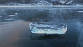 Isisflaket roterar på isen mot bakgrunden av det fantastiska berglandskapet långsam rörelse Kameraflyttningarna stock video