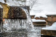 Isistappar på en frysa springbrunn i vinter Arkivbild