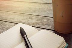 Iskaffe i takeaway kopp med anteckningsboken och penna på sidan Bo arkivbild