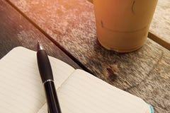 Iskaffe i takeaway kopp med anteckningsboken och penna på sidan Bo fotografering för bildbyråer