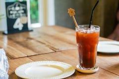 Iskaffe och en maträtt förläggas på en trätabell arkivfoton