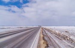 Iskall huvudväg med molniga himlar Arkivbild