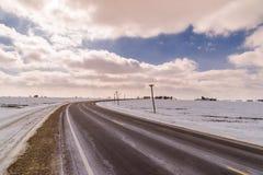 Iskall huvudväg med molniga himlar Royaltyfri Fotografi