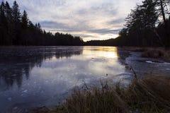 Iskall sötvattensjö i solnedgången Arkivbild