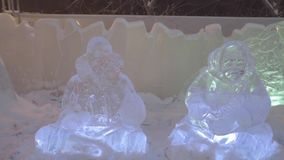 Iskall skulptur av djupfryst sammanträdefolk eller Yakuts i vinterstad Skulptur av sammanträdefolk eller Yakuts som göras av is o stock video