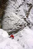 Isklättrare i rött omslag på en dold icefall för brant snö i de schweiziska fjällängarna arkivbilder