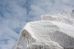 Iskristaller bildade på rockface i vinter mot molnhimmel Arkivfoton