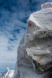 Iskristaller bildade på rockface i vinter mot molnhimmel Arkivbild