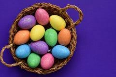 Iskrzaści połyskuje barwionego cukierku Wielkanocni jajka w łozinowym koszu, odgórny widok obrazy royalty free