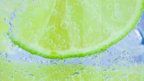 Iskrzasta woda z lodem i plasterka wapnem na białym tle zbiory wideo