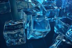 iskuben för tolkningen 3D på blått tonar bakgrund Djupfryst vattenkub Arkivbild