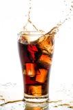 Iskuben tappade, i att plaska för colaexponeringsglas och för cola Arkivfoton