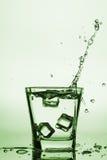 Iskuber som plaskar in i exponeringsglas, iskub, tappade in i exponeringsglas av vatten Royaltyfri Fotografi