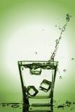 Iskuber som plaskar in i exponeringsglas, iskub, tappade in i exponeringsglas av vatten Arkivfoto