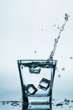 Iskuber som plaskar in i exponeringsglas, iskub, tappade in i exponeringsglas av vatten som var nytt, kallt vatten som isolerades Arkivbilder