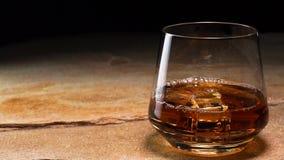 Iskuber upplöser i ett exponeringsglas av whisky eller bourbon stock video