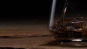 Iskuber upplöser i ett exponeringsglas av whisky eller bourbon lager videofilmer
