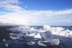 Iskvarter på en svart sandstrand Arkivbilder