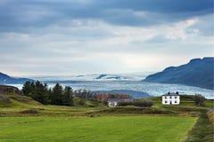 Islândia - em julho de 2008: Paisagem com casa e geleira Imagens de Stock