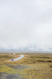 Islândia - em setembro de 2014 - estrada na peça ocidental de Islândia, estrada nebulosa da névoa da névoa, com grama amarela Fotografia de Stock