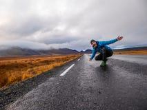 Islândia - homem novo que squatting no meio de uma estrada de anel fotografia de stock royalty free
