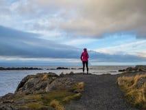 Islândia - uma posição da menina no promontório, observando a paisagem foto de stock