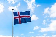 Isländische Flagge, Wolken, blauer Himmel stockbild