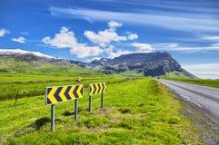 Isländische Landschaft mit grünen Feldern, Bergen und Verkehrsschildern Stockbilder
