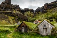 Isländische Rasenhäuser und -felsen mit Wasserfall im Hintergrund lizenzfreie stockfotos