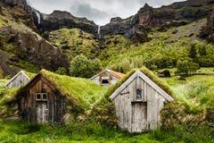 Isländische Rasenhäuser und felsige Schlucht mit Wasserfall im BAC lizenzfreie stockbilder