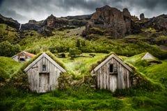 Isländische Rasenhäuser und felsige Schlucht mit Wasserfall im BAC stockbilder
