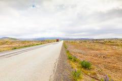Isländische Straße mit rotem LKW Stockfotografie