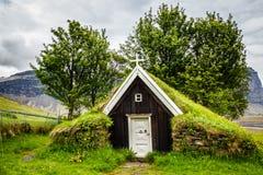 Isländische traditionelle Rasenkirche bedeckt mit Gras, Bäume und lizenzfreie stockfotos