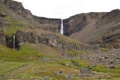 Isländischer Gebirgshoher Wasserfall unter der Sonne Lizenzfreies Stockbild