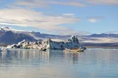 Isländischer Gebirgssee und -gletscher unter der Sonne Stockbilder