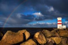 Isländischer Leuchtturm und Regenbogen Lizenzfreies Stockfoto